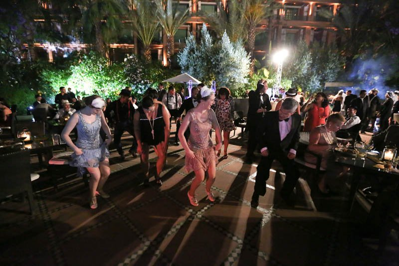 Vintage swing and lindy hop dancers leading a group Charleston at a corporate event with live music in Marrakesh, Morocco