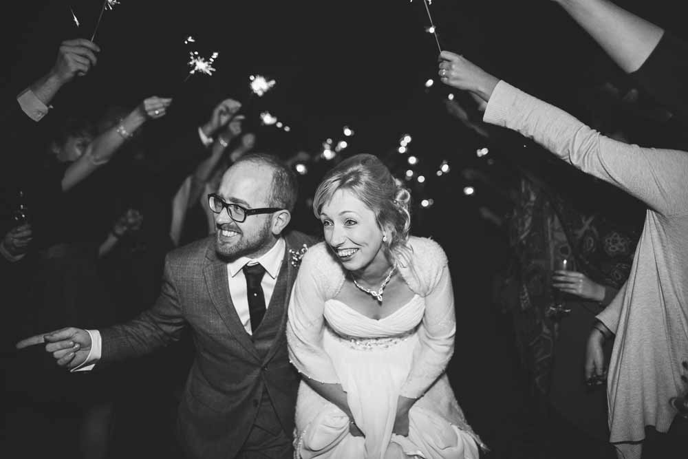 Bride and groom with sparklers at wedding reception in Essex, photo by Indiego Photography